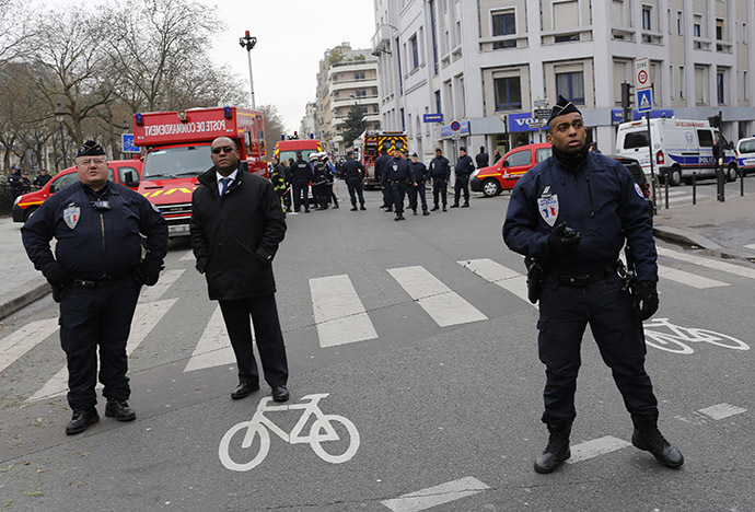 Policemen work at the scene after a shooting at the Paris offices of Charlie Hebdo January 7, 2015. (Reuters/Youssef Boudlal)