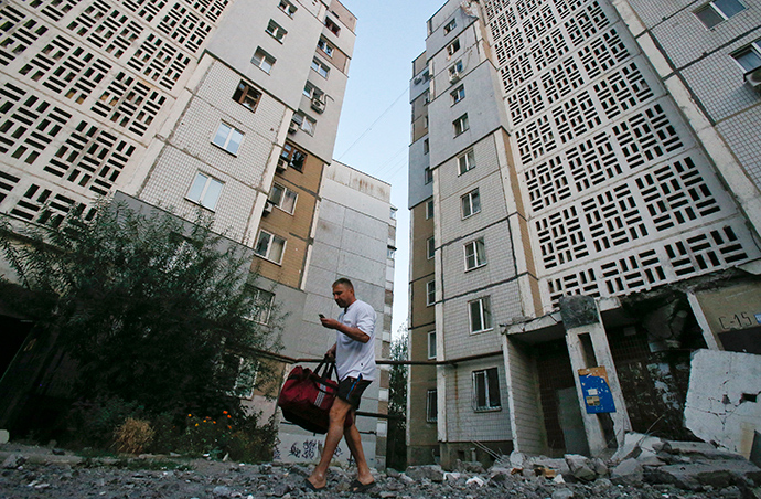 A man walks on rubble near an apartment block damaged by what locals say was shelling by Ukrainian forces in Donetsk (Reuters / Maxim Shemetov)