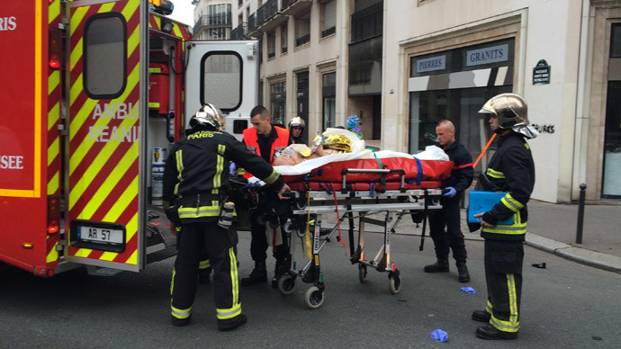 Firefighters carry an injured man on a stretcher in front of the offices of the French satirical newspaper Charlie Hebdo in Paris on January 7, 2015.(AFP Photo / Philippe Dupeyrat)