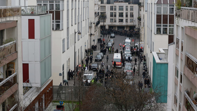 General view of the street where police and fire fighters work in front of the Paris offices of Charlie Hebdo, a satirical newspaper, after a shooting January 7, 2015.(Reuters / Philippe Wojazer )
