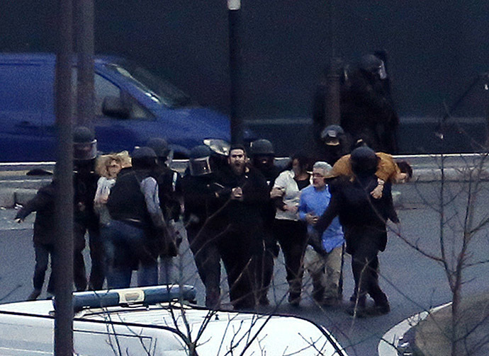 Police evacuate hostages after launching the assault at a kosher grocery store in Porte de Vincennes, eastern Paris, on January 9, 2015. (AFP Photo/Thomas Samson)