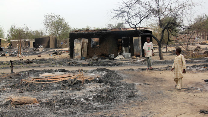 Children walking outside a charrred house in the remote northeast town of Baga, Borno State, after two days of clashes between officers of the Joint Task Force and members of the Islamist sect Boko Haram.(AFP Photo / STR)