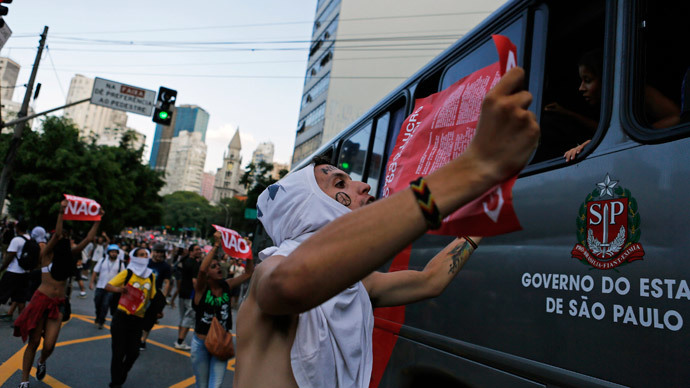 Demonstrators shout slogans in front of a bus during a protest against fare hikes for city buses, subway and trains in Sao Paulo January 9, 2015. (Reuters / Nacho Doce)