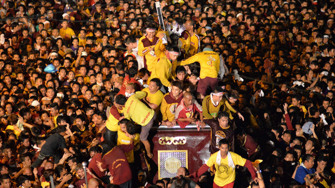 Devotees try to hold the Black Nazarene as it is pulled on a carriage during an annual procession in Manila January 9, 2015. (Reuters / Ezra Acayan)