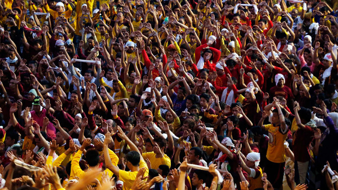 Devotees raise their hands as they pray before the start of the annual procession of the Black Nazarene in Manila, January 9, 2015. (Reuters / Erik De Castro)