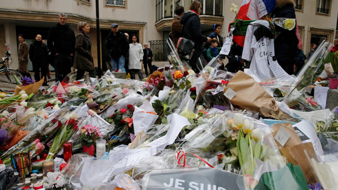 Flowers and messages left by citzens who pay tribute in front of the offices of the weekly satirical newspaper Charlie Hebdo in Paris January 10, 2015.(Reuters / Pascal Rossignol)