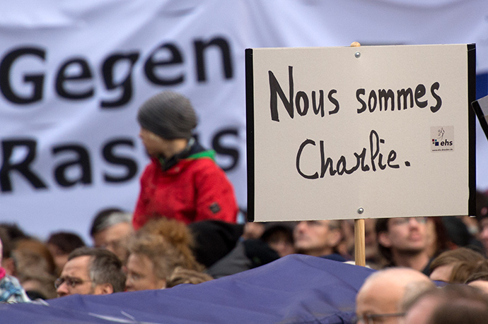 "A poster reading ""Nous sommes Charlie"" (We are Charlie) can be seen as thousands of people take part in a rally themed ""For Dresden, for Saxony - living together in the sense of a global awareness, humanity and dialogue "" on January 10, 2015 in front of the Frauenkirche (Church of Our Lady) in Dresden, eastern Germany (AFP Photo / DPA)"