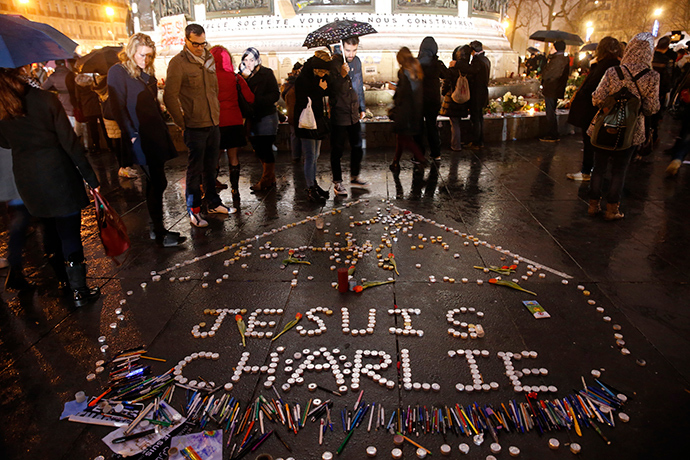 "People gather near candles with the message, ""I am Charlie"" as they continue to pay tribute to the shooting victims on Wednesday at the satirical weekly Charlie Hebdo, at the Republique square in Paris January 10, 2015 (Reuters / Pascal Rossignol)"