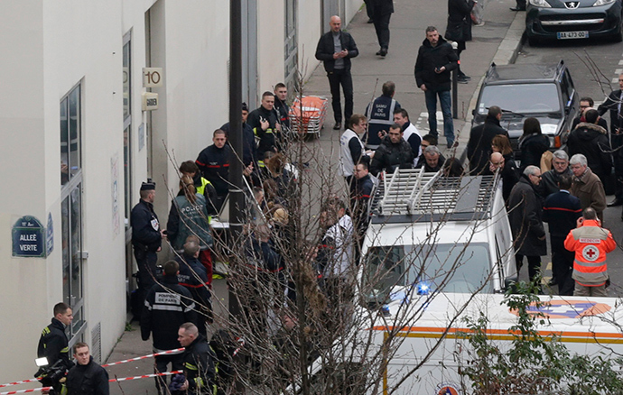 Firefighters and rescue members stand in front of the Paris offices of Charlie Hebdo, a satirical newspaper, after a shooting January 7, 2015 (Reuters / Philippe Wojazer)