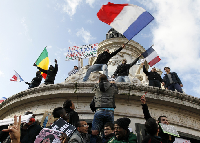 "People holding a poster reading ""Quick more democracy everywhere against barbarism"" take part in a solidarity march (Marche Republicaine) in the streets of Paris January 11, 2015. (Reuters / Youssef Boudlal)"