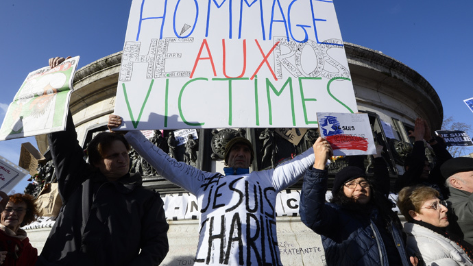 """A man holds a cardboard reading """"Hommage to the Victims-Heros"""" as people gather on the Place de la Republique (Republic Square) in Paris before the start of a Unity rally """"Marche Republicaine"""" on January 11, 2015 (AFP Photo / Bertrand Guay)"""