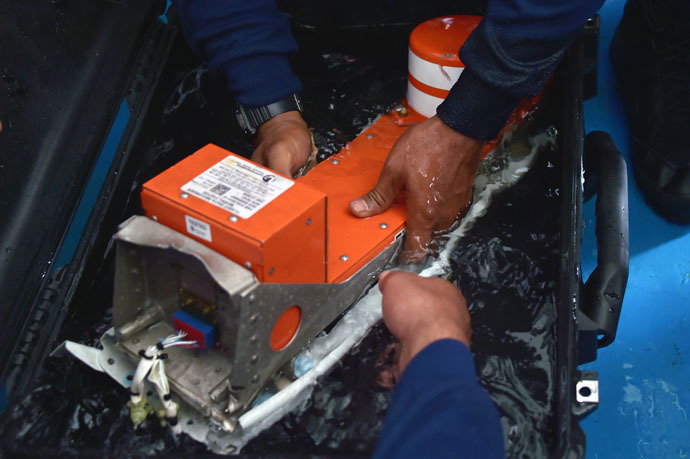 Indonesian divers onboard the Indonesian navy vessel KRI Banda Aceh handle the FDR (Flight Data Recorder) of the AirAsia flight QZ8501 after it was retrieved from the Java Sea on January 12, 2015. (AFP Photo/Adek Berry)