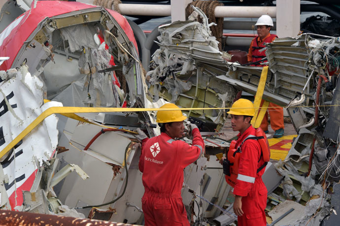 Indonesian crew of the Crest Onyx ship prepare to hoist recovered wreckage of AirAsia flight QZ8501 at port in Kumai on January 11, 2015. (AFP Photo/Adek Berry)