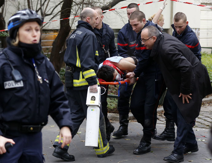 Firefighters carry a victim on a stretcher at the scene after a shooting at the Paris offices of Charlie Hebdo, a satirical newspaper, January 7, 2015. (Reuters/Jacky Naegelen)