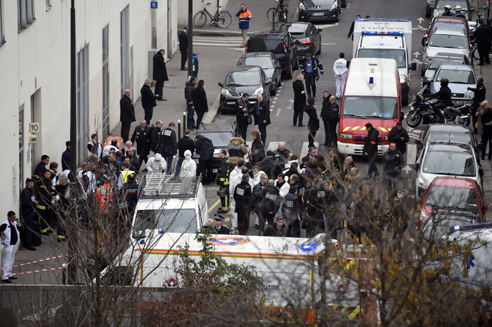 Firefighters, police officers and forensics gathered in front of the offices of the French satirical newspaper Charlie Hebdo after armed gunmen stormed the building leaving twelve dead. (AFP Photo)