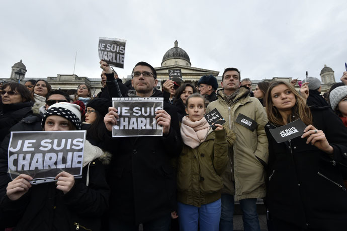 """People hold signs that reads """"Je suis Charlie"""" (I am Charlie) and pens during a gathering in Trafalgar Square in central London on January 11, 2015 to commemorate the victims of the attacks in France that killed 17 people and injured scores more. (AFP Photo)"""
