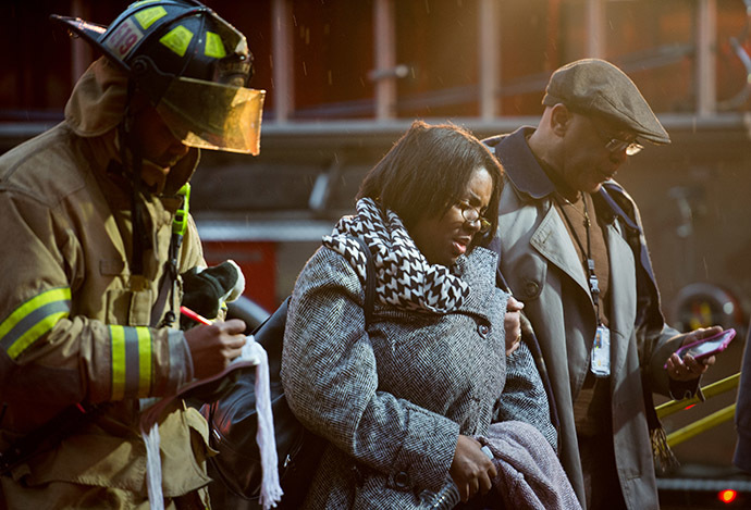 Smoke inhalation victims walk past a firefighter towards a medical aid bus after passengers on the Metro (subway) were injured when smoke filled the L'Enfant Plaza station during the evening rush hour January 12, 2015 in Washington, DC. (AFP Photo/Paul J. Richards)