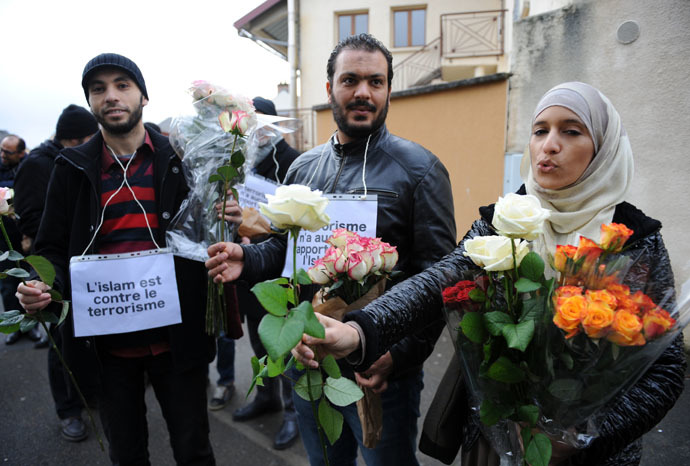 "Muslims with placards reading ""Islam is against terrorism"" offer roses in the Sablons neighborhood of Le Mans, western France, on January 10, 2015, in front of the mosque against which bullets were fired and 3 grenades launched on January 8. (AFP Photo)"