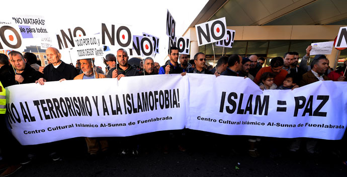 "Muslims hold banners reading ""No to terrorism and to Islamophobia "" and ""Islam = Peace"" in Madrid on January 11, 2015. (AFP Photo)"