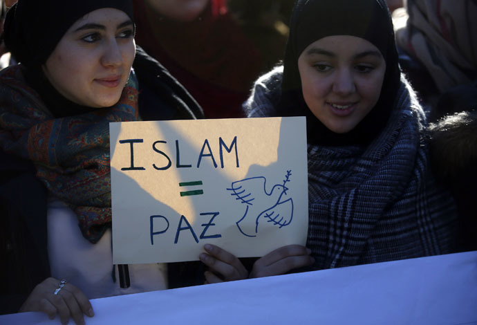 """Two young women hold a placard that reads """"Islam = Peace"""" in Madrid on January 11, 2015. (Reuters)"""