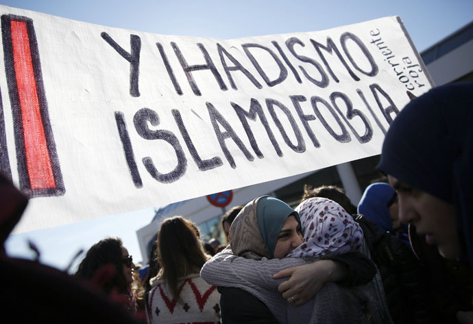 "Two women embrace under a banner that reads, ""No to Islamophobia and jihadism"" during a rally outside Madrid's Atocha train station on January 11, 2015. (Reuters)"
