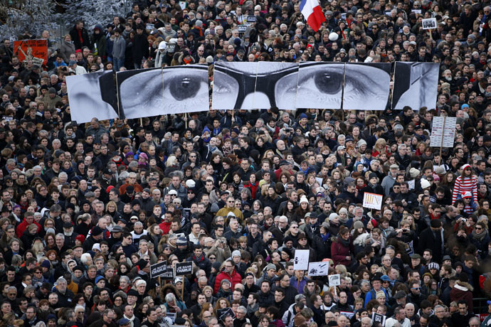 """eople hold panels to create the eyes of late Charlie Hebdo editor Stephane Charbonnier, known as """"Charb"""", as hundreds of thousands of French citizens take part in a solidarity march (Marche Republicaine) in the streets of Paris January 11, 2015. (Reuters/Charles Platiau)"""