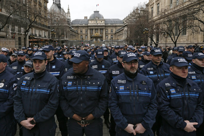 French municipal Police officers react as they attend a national tribute for the three officers killed during last week's terrorist attacks, in front of Paris Prefecture, January 13, 2015. (Reuters/Gonzalo Fuentes)