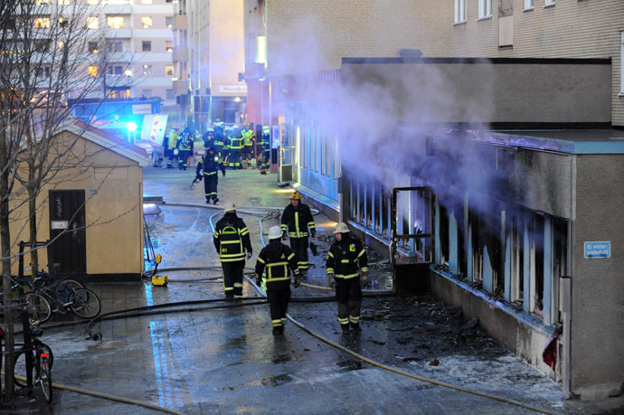 Smoke rises from the interior of a destroyed cellar mosque as firefighters walk in front of the building after an arson attack on December 25, 2014 in Eskilstuna, central Sweden. (AFP/TT News Agency)