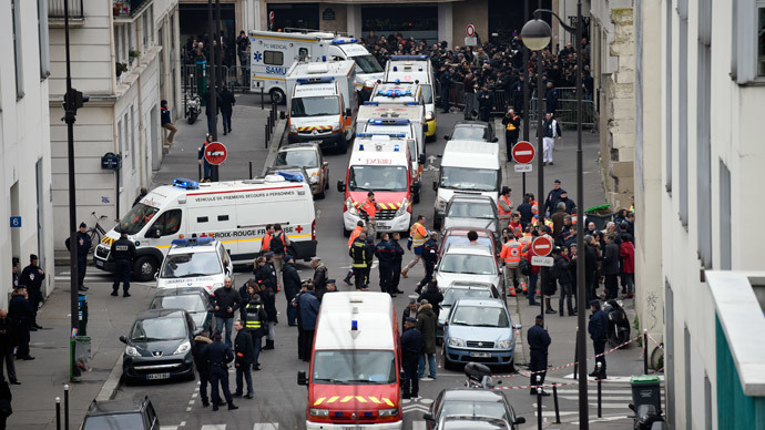 A general view shows firefighters, police officers and forensics gathered in front of the offices of the French satirical newspaper Charlie Hebdo in Paris on January 7, 2015.(AFP Photo / Martin Bureau)