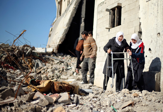 Palestinian girl Manar Al-Shinbari (2nd R), 15, who lost both her legs in what medics said was Israeli shelling at a UN-run school where she was taking refuge during the 50-day war last summer, uses her walker at the ruins of her house that witnesses said was destroyed by Israeli shelling during the war, in Biet Hanoun in the northern Gaza Strip January 13, 2015. (Reuters / Mohammed Salem)