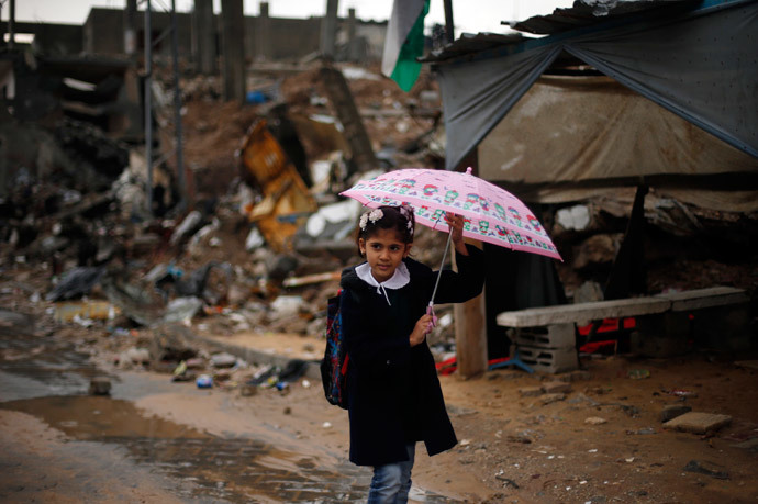 A Palestinian school girl holds an umbrella as she walks near the ruins of houses that witnesses said were destroyed by Israeli shelling during the most recent conflict between Israel and Hamas (Reuters / Suhaib Salem)
