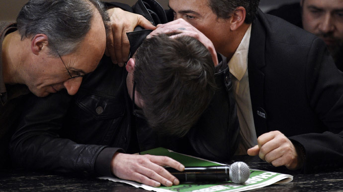 French cartoonist Renald Luzier, aka Luz (C), is comforted by editor in chief of French satirical weekly Charlie Hebdo Gerard Briard (L) and editorialist Dr Patrick Pelloux, during a press conference to present the new issue of the weekly at the offices of French newspaper Liberation in Paris on January 13, 2015. (AFP Photo / Martin Bureau)