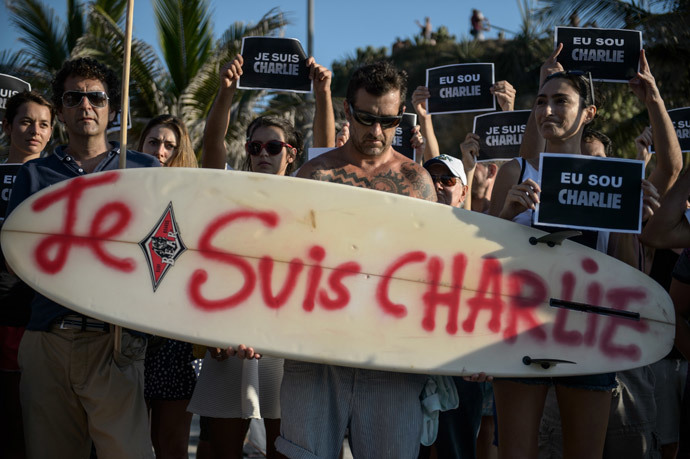 "A man holds a surfboard reading ""I am CHARLIE"" during a rally at Arpoador beach in Rio de Janeiro, Brazil on January 11, 2015 in tribute to the 17 victims of this week's Islamist attacks in France (AFP Photo / Yasuyoshi Chiba)"