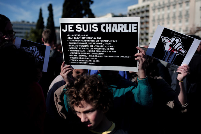 "A woman holds a sign reading ""je suis Charlie"" and the list of the journalists who were killed in the attack on the offices of Charlie Hebdo, in front of the Greek Parliament in Athens on January 11, 2015 (AFP Photo / Angelos Tzortzinis)"