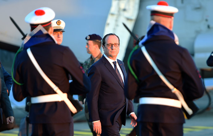 French President Francois Hollande reviews the troops during his visit on the French nuclear aircraft carrier Charles de Gaulle to present his New Year wishes to the French military forces, on January 14, 2015 off the coast of Toulon, southern France. (AFP Photo / Pool / Anne-Christine Poujoulat)