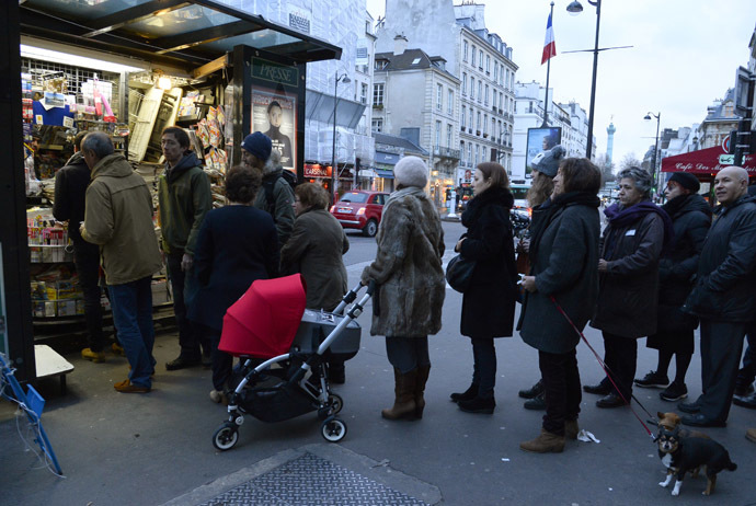 People wait outside a newsagents kiosk in Paris on January 14, 2015 as the latest edition of French satirical magazine Charlie Hebdo went on sale. (AFP Photo/Bertrand Guay)