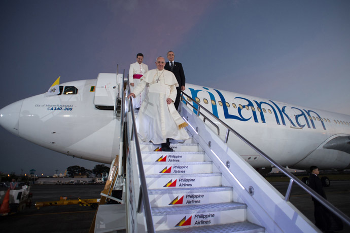 In this handout picture released by the Vatican press office (Osservatore Romano), Pope Francis (C) arrives in the Philippines in Manila on January 15, 2015. (AFP Photo/Osservatore Romano)