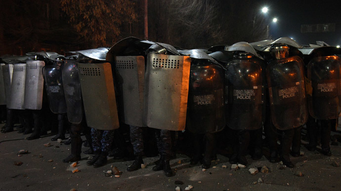 Armenian police officers hold up their shields as they stand guard during clashes with protesters at a demonstration near the Russian Consulate General in Gyumri, north-western Armenia, on January 15, 2015.(AFP Photo / Karen Minasyan)