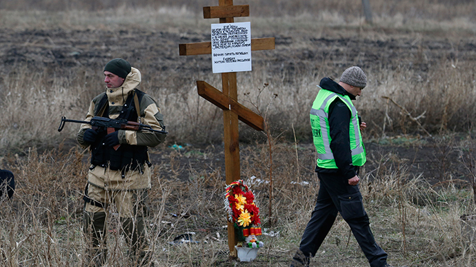 A member of the recovery team works at the site where the downed Malaysia Airlines flight MH17 crashed as an armed security representing the self-proclaimed Donetsk People's Republic stands guard near a cross erected by local residents in memory of victims (Reuters / Maxim Zmeyev)