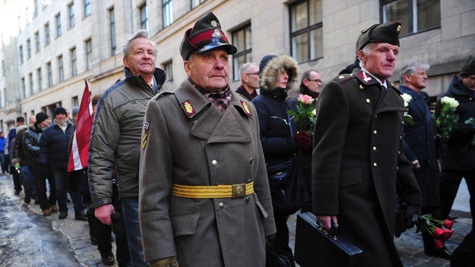 Two man dressed in pre-WWII Latvian military uniforms walk along with veterans of the Latvian Legion, a force that was commanded by the German Nazi Waffen SS, and their sympathizers to the Monument of Freedom in Riga, Latvia.(AFP Photo / Ilmars Znotins)