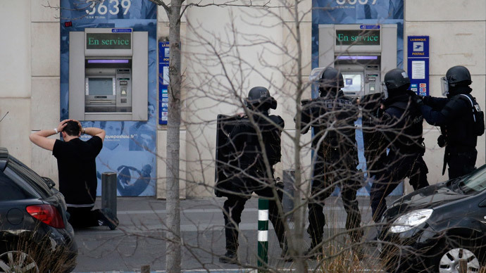 A suspect in a hostage taking situation is detained by members of special French RAID forces outside the post offices in Colombes outside Paris, January 16, 2015.(Reuters / Philippe Wojazer)