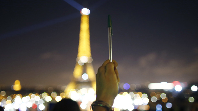 A person holds a pen, symbolising freedom of speech, as lights on the Eiffel Tower start to dim before switching off for five minutes January 8, 2015 in tribute to journalists of the weekly satirical newspaper Charlie Hebdo after a shooting at their offices. (Reuters / Charles Platiau)