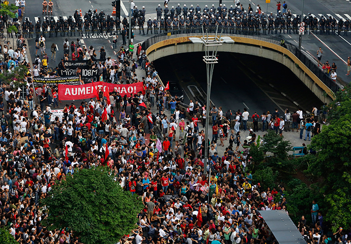 Demonstrators march in front of a line of riot police during a protest against fare hikes for city buses, subway and trains in Sao Paulo January 16, 2015 (Reuters / Nacho Doce)