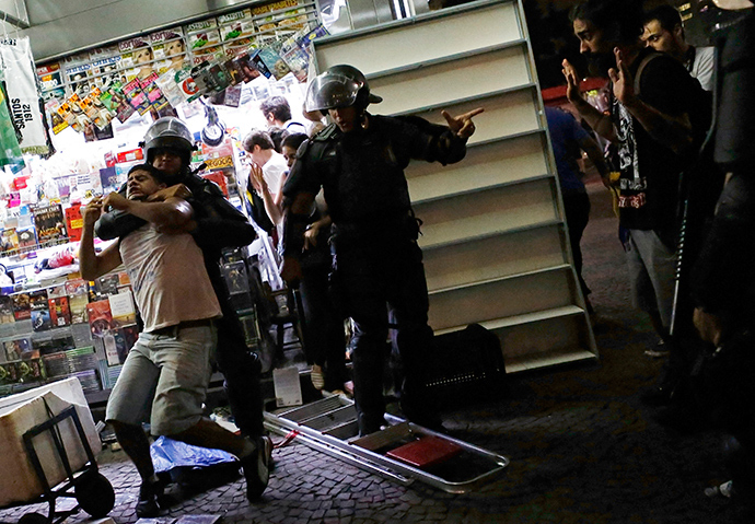 Riot police detain a demonstrator during a protest against fare hikes for city buses, subway and trains in Sao Paulo January 16, 2015 (Reuters / Nacho Doce)