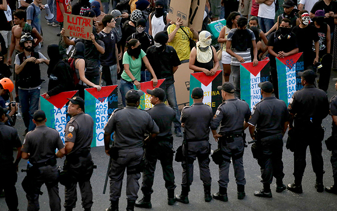 Riot police block a street as demonstrators use makeshift shields painted with the colours of the Palestinian flag during a protest against fare hikes for city buses in Rio de Janeiro January 16, 2015 (Reuters / Mauro Pimentel)