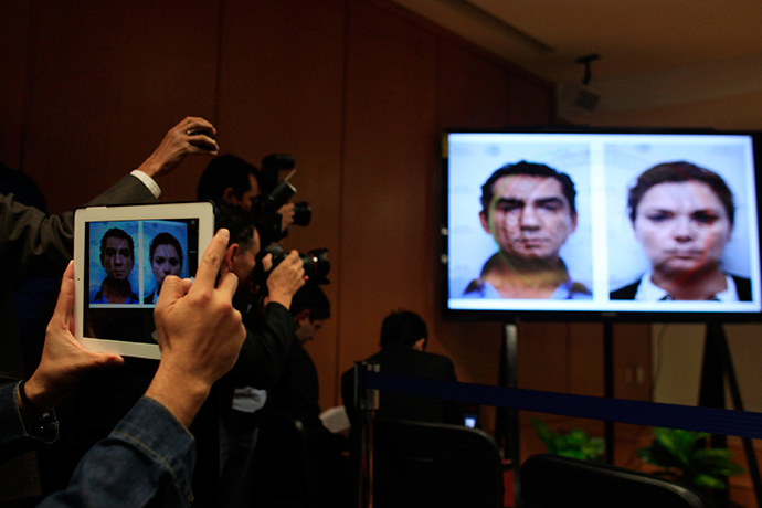 Media take pictures of mugshots of Jose Luis Abarca, former mayor of Iguala, and his wife Maria de los Angeles displayed on a screen during a news conference in Mexico City December 7, 2014 (Reuters / Carlos Jasso)