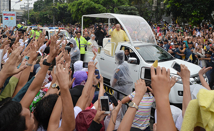 Pope Francis, wearing a raincoat, waves to well-wishers during a meeting with youths at the University of Santo Tomas (UST) in Manila January 18, 2015 (Reuters / Ezra Acayan)