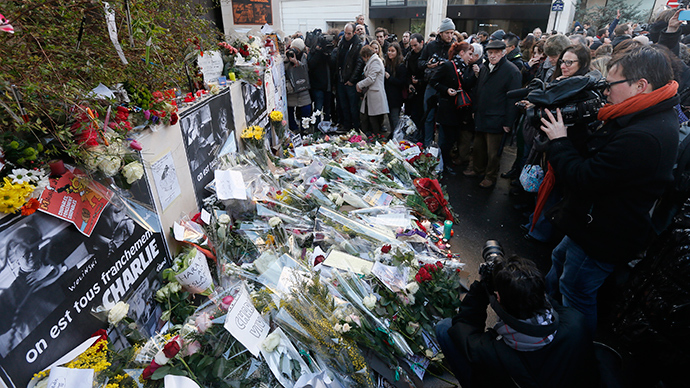 Journalists and citizens surround flowers placed in front of the offices of weekly satirical newspaper Charlie Hebdo in Paris (Reuters / Gonzalo Fuentes)