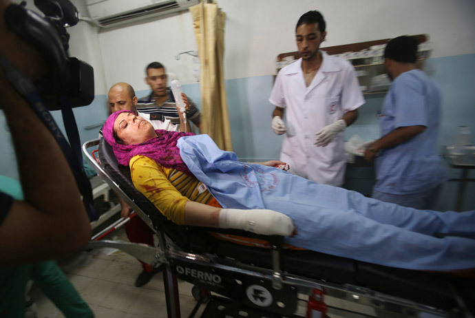 A Palestinian woman who, medics said, was wounded in an Israeli air strike arrives at a hospital in Khan Younis in the southern Gaza Strip July 8, 2014. (Reuters / Ibraheem Abu Mustafa)