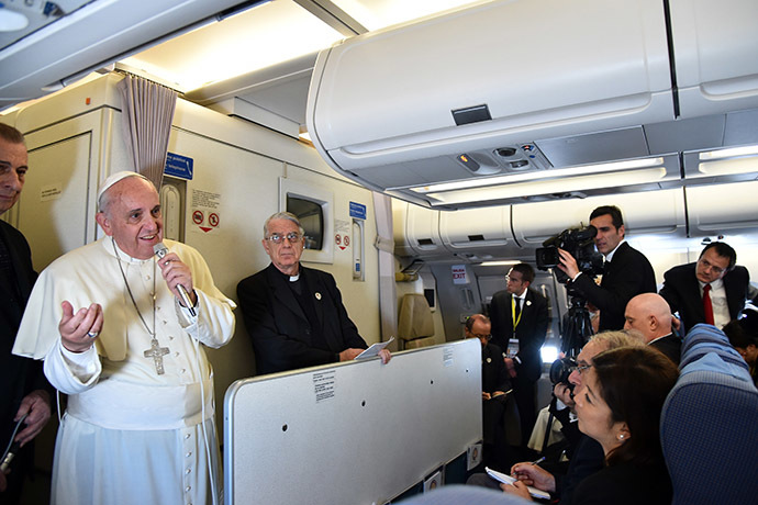 Pope Francis addresses journalist sitting onboard a plane during his trip back to Rome, on January 19, 2015 from the Philippines. (AFP Photo/Giuseppe Cacace)
